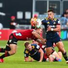 Highlanders centre Rob Thompson is tackled by opposite Brayden Ennor as Highlanders flanker and...