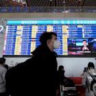 A traveller wearing a mask walks past a departures information board at Beijing International...