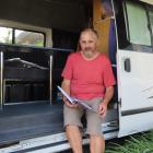 Tony Adams checks through the log book that contains his and Diane's camper van adventures.
