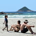 Odom, of Brighton, lean against each other to sunbathe while their son Thomas (3) plays on the...