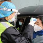 A security officer in a protective mask checks the temperature of a passenger following the...