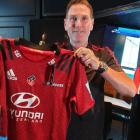 Crusaders fan Anthony Mercer holds a jersey with the team's new logo. Photo: RNZ/Anan Zaki