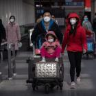 Mask-wearing travellers at Beijing Capital Airport. Photo: Getty