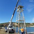 A telehandler is used to take the Oamaru Harbour breakwater navigational aid away to be treated...