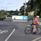 A cyclist waits to cross Portsmouth Dr near the Otago Peninsula map lay­by area on Tuesday. PHOTO...