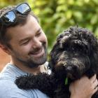 Sybil the spoodle is comforted by Dunedin man Gareth Lea after her big day out on Saturday....