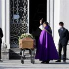 A priest blesses the coffin of a coronavirus victim at her funeral in Seriate, Italy. Photo:...