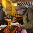 Fred Mursa signs a register of patrons at Inch Bar, in North East Valley, on Saturday. PHOTO:...