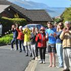 Clapping for essential workers while practising social distancing, standing 2m apart, are...