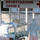 Medical workers in protective suits push an isolation stretcher in front of the Columbus Clinic,...