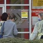 Dunedin Hospital staff wearing protective gear escort two patients through the main entrance of...