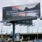 A billboard at LAX promoting non-stop flights from LA to Christchurch features a backdrop of...