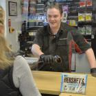 Callum Macarthur serves another customer at the Challenge Fitzroy service station yesterday under...