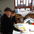 Stained glass specialist Peter Mackenzie (left) and artist Jenna Packer discuss the placement of...