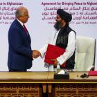 Mullah Abdul Ghani Baradar, the leader of the Taliban delegation, and Zalmay Khalilzad, U.S....
