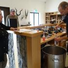 Cardrona Distillery ambassador Sam Bickley pours free alcohol hand sanitiser into a container for...