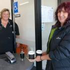 Claire Wilson, of Balclutha, picks up two cappuccinos from Heart & Soul Cafe owner Robyn Bell...