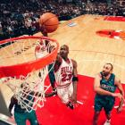 Michael Jordan takes the ball to the hoop against the Charlotte Hornets in his last season with...