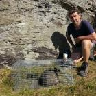 Forest & Bird volunteer Billy Stephen Barton beside a feral cat caught in a satellite...