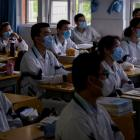 Students wearing masks attend classes at a high school in Wuhan in central China's Hubei province...