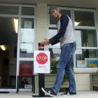 Maheno School principal Ryan Fraser tries out the foot-operated dispenser made by Oamaru's Anvil...