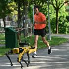 A man jogs past a four-legged robot called Spot, which broadcasts a recorded message reminding...