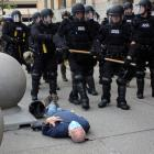 Martin Guginolays on the ground after he was shoved by two police officers. Photo: Jamie King via...