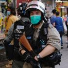 Riot police stand guard to avoid mass gathering during a protest against the looming national...