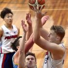 Falcon player Alex Yarnall gets up a shot despite the attention of University duo Sam Seelan ...
