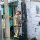A Kaitangata homeowner looks on as firefighters damp down hotspots at the side of her...
