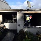 Fire investigator Mark Bredenbeck sorts through the remains of Thursday night's fire at the...