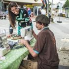 Wastebusters baler Bruce Shanks gets some bag-making advice from solar sewer Sarah Lancaster, on...