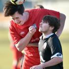 Caversham midfielder Olivier Cassidy gets up for a header, despite the attention of Dunedin...