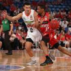 Jarrod Kenny (left), playing for the Cairns Taipans, keeps Bryce Cotton of the Wildcats in check...