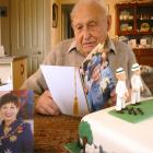 Lionel Woods reads a card from The Queen wishing him a happy 100th birthday, 