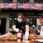 A waitress with a face mask serves diners at a restaurant in Alexandria, Virginia. Photo: Reuters