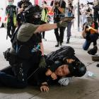 Police officers detain a man during a march against the national security law in Hong Kong. Photo...