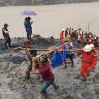Rescuers carry a body following the landslide at a mining site in Hpakant, Kachin State City,...