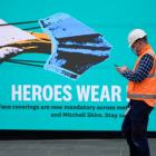 An essential worker walks past a 'Heroes Wear Masks' sign in Melbourne after it became the first...