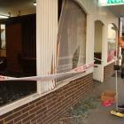 Gin's Restaurant owner Jimmy Au Yeung cleans up debris after a ute slid on ice and crashed into...