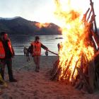 Tom Winder puts a torch to one of the piles of driftwood on the shore of Lake Wanaka on Saturday....