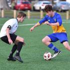 University forward Ben Stanley (right) tries to go past Roslyn Wakari defender Jack Stevenson at...