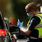 A police officer speaks with a motorist in Melbourne as the city prepares to go back into Covid...