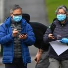 People in face masks on a city street in Melbourne. Masks or coverings will be mandatory for many...
