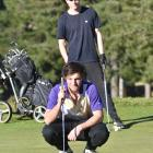 University of Otago students Toby Rainger (front) and Oscar Acland study the line of a putt at...