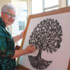 Celebrant Lynley McKerrow writes the name of a loved one on a branch of the Tree of Life. PHOTOS:...