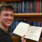 Conor Hassan holds his great-grandfather Miles Barnett's master's thesis in the physics archives...