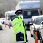 Police stop vehicles at a checkpoint on State Highway 1 near Wellsford north of Auckland on...