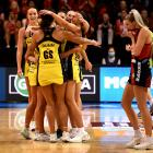 Pulse players celebrate their victory as dejected Tactix captain Watson trudges off the court...
