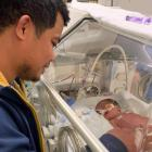 Heylon Sevilla, keeps a watchful eye on newborn daughter Estella Marie while he waits for news on...